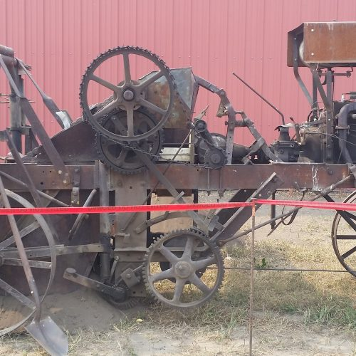 1946 Trenching Machine built by John Fraser of Huxley, AB. Notice the open gear mechanisms which were a hazard to the safety of the operator. This unit also required an anchor point to move it along the ditch line. — at Pioneer Acres Museum.