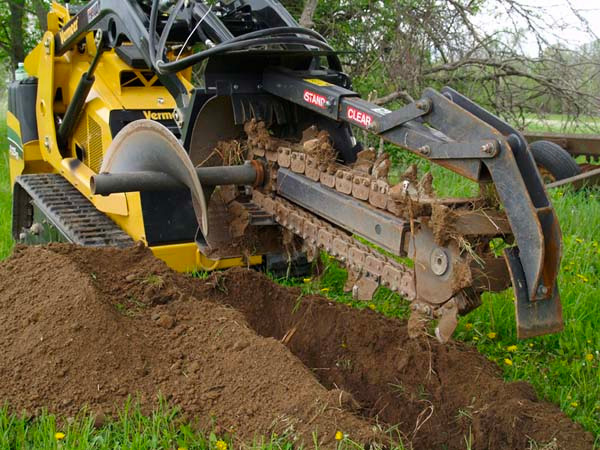 Trencher Attachment Fits on the front of a skidsteer to perform larger trenching projects. This unit is able to trench a ditch 4 feet deep and 6 inches wide at a speed of up to 100 feet per hour. Such a difference from the 1946 version!